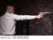 Купить «Serious hired murderer in red tie aims a gun», фото № 30564683, снято 19 января 2017 г. (c) Tryapitsyn Sergiy / Фотобанк Лори