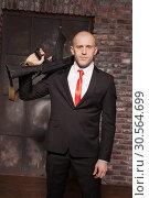 Купить «Assassin in suit and red tie holding machine gun», фото № 30564699, снято 19 января 2017 г. (c) Tryapitsyn Sergiy / Фотобанк Лори