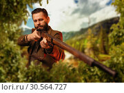 Hunter sitting in the bushes and aiming a rifle. Стоковое фото, фотограф Tryapitsyn Sergiy / Фотобанк Лори