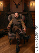 Hunter man sitting in a chair and drink whiskey. Стоковое фото, фотограф Tryapitsyn Sergiy / Фотобанк Лори