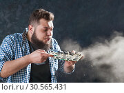 Male engineer blows off the dust from motherboard. Стоковое фото, фотограф Tryapitsyn Sergiy / Фотобанк Лори