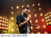 Brutal bearded singer with microphone sing a song. Стоковое фото, фотограф Tryapitsyn Sergiy / Фотобанк Лори