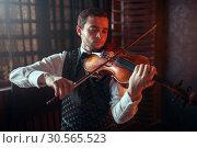 Купить «Male violinist playing classical music on violin», фото № 30565523, снято 4 марта 2017 г. (c) Tryapitsyn Sergiy / Фотобанк Лори