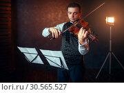 Купить «Male violinist with violin against music stand», фото № 30565527, снято 4 марта 2017 г. (c) Tryapitsyn Sergiy / Фотобанк Лори