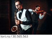 Sax man and fiddler duet playing classical melody. Стоковое фото, фотограф Tryapitsyn Sergiy / Фотобанк Лори