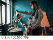 Painter looking at canvas painting against poseur. Стоковое фото, фотограф Tryapitsyn Sergiy / Фотобанк Лори