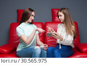 Two girlfriends looking at pictures on phone. Стоковое фото, фотограф Tryapitsyn Sergiy / Фотобанк Лори