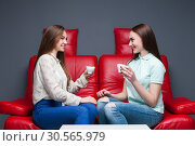 Two laughing girlfriends drinking coffee. Стоковое фото, фотограф Tryapitsyn Sergiy / Фотобанк Лори