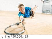 Купить «Squash training, player with racket lies on floor», фото № 30566483, снято 26 апреля 2017 г. (c) Tryapitsyn Sergiy / Фотобанк Лори