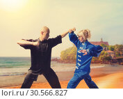 Купить «Male and female wushu fighters training on coast», фото № 30566827, снято 26 мая 2017 г. (c) Tryapitsyn Sergiy / Фотобанк Лори
