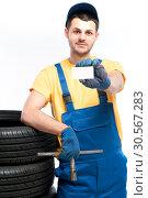 Купить «Worker holds tire and empty businesscard in hands», фото № 30567283, снято 22 июня 2017 г. (c) Tryapitsyn Sergiy / Фотобанк Лори