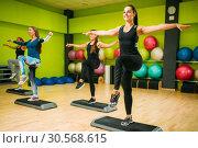 Athletic women on step aerobic training indoor. Стоковое фото, фотограф Tryapitsyn Sergiy / Фотобанк Лори