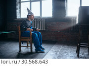 Afraided man in aluminum foil helmet sits in chair. Стоковое фото, фотограф Tryapitsyn Sergiy / Фотобанк Лори