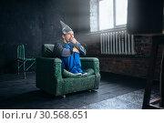 Stupid man in tinfoil helmet watch TV, UFO phobia. Стоковое фото, фотограф Tryapitsyn Sergiy / Фотобанк Лори