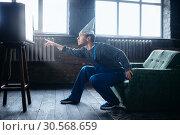 Купить «Strange man in tinfoil cap reaches out to TV, UFO», фото № 30568659, снято 1 октября 2017 г. (c) Tryapitsyn Sergiy / Фотобанк Лори