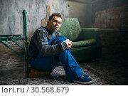 Купить «Depressed man sitting on the floor, psycho patient», фото № 30568679, снято 1 октября 2017 г. (c) Tryapitsyn Sergiy / Фотобанк Лори