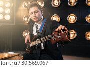 Купить «Rock guitarist in suit playing on bas-guitar», фото № 30569067, снято 10 ноября 2017 г. (c) Tryapitsyn Sergiy / Фотобанк Лори