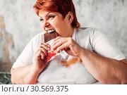 Купить «Overweight woman eats chocolate, obesity», фото № 30569375, снято 23 ноября 2017 г. (c) Tryapitsyn Sergiy / Фотобанк Лори