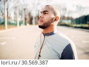 Athlete in headphones before jogging in park. Стоковое фото, фотограф Tryapitsyn Sergiy / Фотобанк Лори