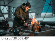 Stalker, male person cooking canned food on fire. Стоковое фото, фотограф Tryapitsyn Sergiy / Фотобанк Лори