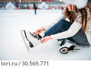 Young woman ties the shoelaces on skates. Стоковое фото, фотограф Tryapitsyn Sergiy / Фотобанк Лори