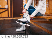 Female person sitting on bench and wears skates. Стоковое фото, фотограф Tryapitsyn Sergiy / Фотобанк Лори