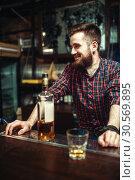 Купить «One man standing at the bar counter, drunkenness», фото № 30569895, снято 20 декабря 2017 г. (c) Tryapitsyn Sergiy / Фотобанк Лори