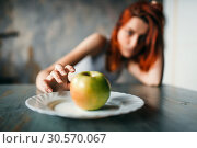 Female hand reaches plate with apple. Стоковое фото, фотограф Tryapitsyn Sergiy / Фотобанк Лори