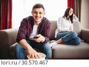 Man watch tv and eats popcorn, woman in a bad mood. Стоковое фото, фотограф Tryapitsyn Sergiy / Фотобанк Лори
