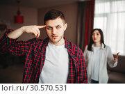 Купить «Husband put finger to temple, wife yells at him», фото № 30570531, снято 11 февраля 2018 г. (c) Tryapitsyn Sergiy / Фотобанк Лори