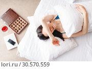 Купить «Woman lies under the blanket, top view, depression», фото № 30570559, снято 11 февраля 2018 г. (c) Tryapitsyn Sergiy / Фотобанк Лори