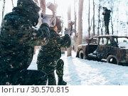 Купить «Paintball players shooting at enemy, winter battle», фото № 30570815, снято 25 февраля 2018 г. (c) Tryapitsyn Sergiy / Фотобанк Лори