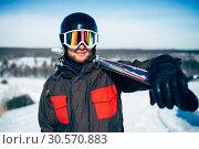 Купить «Skier holds skis and poles in hands», фото № 30570883, снято 6 марта 2018 г. (c) Tryapitsyn Sergiy / Фотобанк Лори