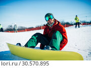 Snowboarder in glasses sitting on snowy slope. Стоковое фото, фотограф Tryapitsyn Sergiy / Фотобанк Лори