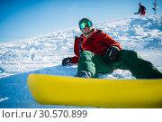 Купить «Snowboarder in glasses poses with board in hands», фото № 30570899, снято 6 марта 2018 г. (c) Tryapitsyn Sergiy / Фотобанк Лори