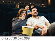 Купить «Couple fascinated watching the film in cinema», фото № 30570999, снято 21 марта 2018 г. (c) Tryapitsyn Sergiy / Фотобанк Лори