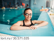 Купить «Smiling female swimmer in goggles swims in pool», фото № 30571035, снято 28 марта 2018 г. (c) Tryapitsyn Sergiy / Фотобанк Лори