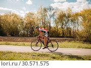 Cyclist rides on bicycle, side view. Стоковое фото, фотограф Tryapitsyn Sergiy / Фотобанк Лори