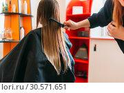 Купить «Hairdresser runs the comb, female client», фото № 30571651, снято 29 апреля 2018 г. (c) Tryapitsyn Sergiy / Фотобанк Лори