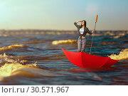 Купить «Cute woman travels by sea on big inverted umbrella», фото № 30571967, снято 24 мая 2018 г. (c) Tryapitsyn Sergiy / Фотобанк Лори
