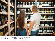 Young couple looking for wine in alcohol market. Стоковое фото, фотограф Tryapitsyn Sergiy / Фотобанк Лори