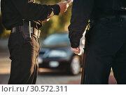 Купить «Cops in uniform check the car on road», фото № 30572311, снято 6 июня 2018 г. (c) Tryapitsyn Sergiy / Фотобанк Лори