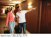 Couple with suitcases looking for their hotel room. Стоковое фото, фотограф Tryapitsyn Sergiy / Фотобанк Лори