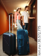 Купить «Suitcases in hotel hallway, couple open the door», фото № 30572775, снято 30 июня 2018 г. (c) Tryapitsyn Sergiy / Фотобанк Лори