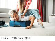 Купить «Cheerful girl packed her husband in a suitcase», фото № 30572783, снято 30 июня 2018 г. (c) Tryapitsyn Sergiy / Фотобанк Лори