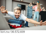 Купить «Man lies on overfilled suitcase, fees on journey», фото № 30572839, снято 30 июня 2018 г. (c) Tryapitsyn Sergiy / Фотобанк Лори