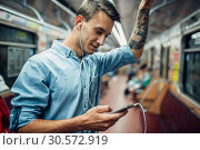 Купить «Young man using phone in metro, addicted people», фото № 30572919, снято 3 июля 2018 г. (c) Tryapitsyn Sergiy / Фотобанк Лори
