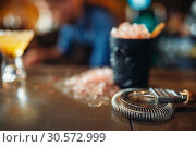 Купить «Black glass with ice, cold crystals on bar counter», фото № 30572999, снято 6 июля 2018 г. (c) Tryapitsyn Sergiy / Фотобанк Лори
