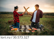 Playful couple fight on loaves, picnic in field. Стоковое фото, фотограф Tryapitsyn Sergiy / Фотобанк Лори