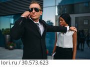 Bodyguard requests support for client protection. Стоковое фото, фотограф Tryapitsyn Sergiy / Фотобанк Лори